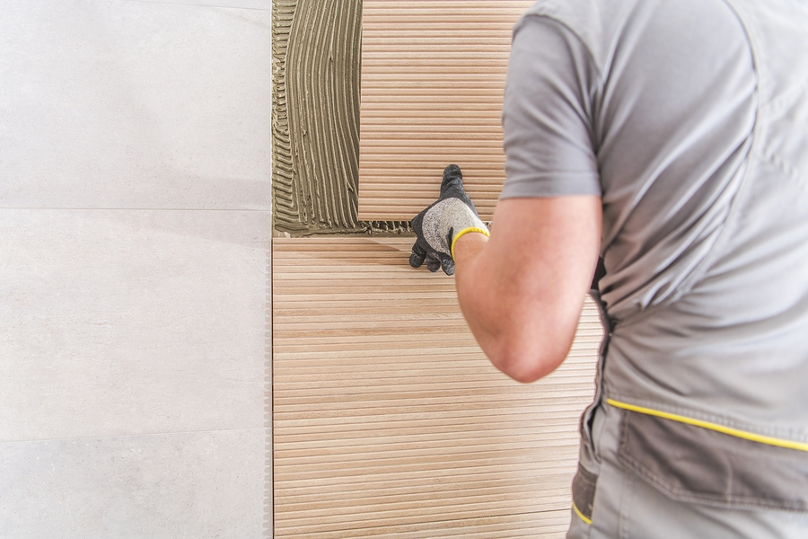 worker installing a wall tile